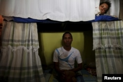 Inmate Alvis Javier (L), poses for a photograph as another prisoner looks from his bunk inside the transgender gallery in La Joya prison on the outskirts of Panama City, Panama, Jan. 27, 2016.