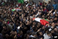 Palestinians carry the bodies of Ahmed Abu al-Aish, 28, and Laith Manasrah, 21, during their funeral in the Qalandia refugee camp on the outskirts of the West Bank city of Ramallah, Nov. 16, 2015.