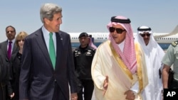 U.S. Secretary of State John Kerry, left, is greeted by Saudi Foreign Minister Prince Saud al-Faisal upon arrival in Jeddah, Saudi Arabia, June 25, 2013.