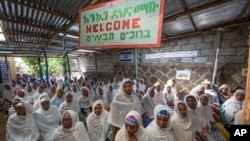 "Members of Ethiopia's Jewish community gather below a banner reading ""Welcome"" in Amharic, English and Hebrew, to protest the Israeli decision not to allow all of them to emigrate to Israel, leaving their families divided between the two countries, in Addis Ababa, Nov. 19, 2018."
