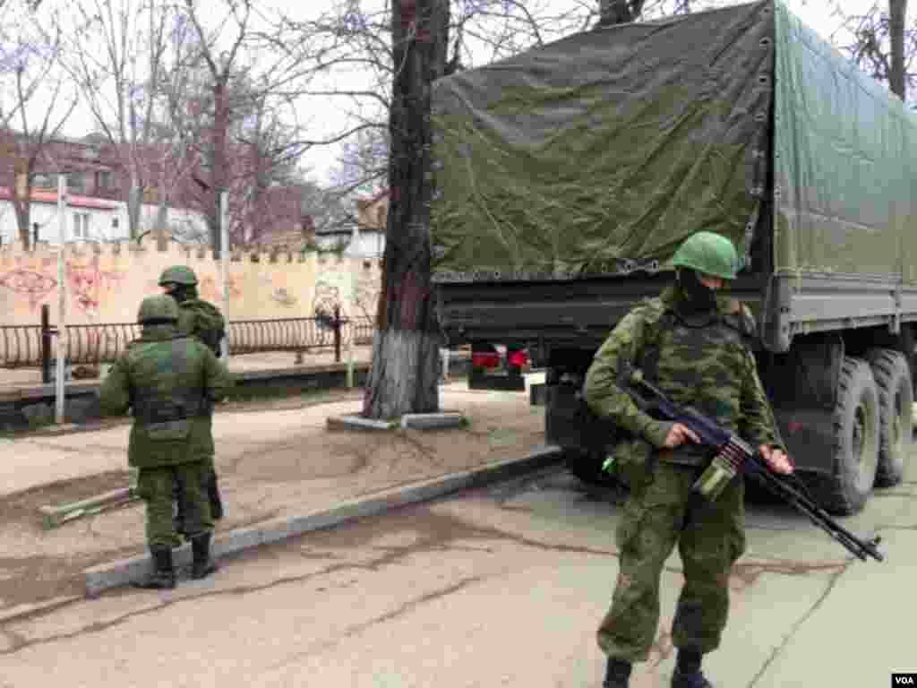 Soldiers without insignia guard buildings in the Crimean capital, a day after the Crimean prime minister called for Russian help on March 2, 2014 in Simferopol. (E Arrott/VOA)