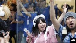 Konsumen meluapkan kegembiraan mereka saat Apple Inc. mulai menjual iPhone 5 di sebuah toko di Tokyo, Jumat pagi (21/9).