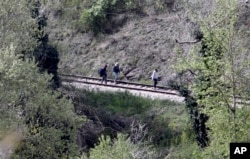 Near the site where 14 migrants were killed by a train, others walk along tracks north of the central Macedonian town of Veles, April 24, 2015.