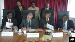 In this photo taken by International Criminal Court, first row from left: Kenya's Justice Minister Mutula Kilonzo, ICC's prosecutor Luis Moreno-Ocampo, Kenya's Minister of Lands James Orengo, as they sign an agreement at ICC in The Hague, Netherlands, Jul