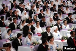 Brides and bridegrooms wait for the start of their wedding ceremony in Ankara, August 6, 2006.