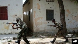 Somali government forces run in a street during skirmishes with insurgents from the al-Qaida aligned terrorist group Al-Shabaab in the Wardigley neighborhood in Mogadishu, Somalia, Monday, Sept. 27, 2010. (AP Photo/ Mohamed Sheikh Nor)