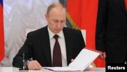 Ruski predsednik Vladimir Putin potpisuje sporazum o ratifikaciji sporazuma kojim Krim postaje deo Rusije na ceremoniji u Kremlju 21. marta 2014.