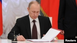 Russian President Vladimir Putin prepares to sign a law on ratification of a treaty making Crimea part of Russia, March 21, 2014.