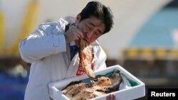 PM Jepang Shinzo Abe menunjukkan bahwa makanan di Fukushima sudah bebas radiasi dengan makan ikan bakar di pelabuhan Soma, Fukushima (foto: dok).