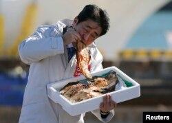 Thủ tướng Nhật Shinzo Abe ăn cá nướng tại cảng Soma Haragama ở Fukushima. Tất cả sản phẩm trong khu vực này đều được thử nghiệm chất đồng vị cesium.