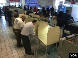 People vote at a polling location in Chicago's Precinct 6 Ward 45, inside a Nissan dealership on Irving Park Road in Illinois, March 15, 2016. (K. Farabaugh/VOA)