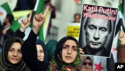 Turkish protesters shout anti-Russia slogans as they hold a poster of Russian President Vladimir Putin during a protest in Istanbul, Turkey, Nov. 27, 2015. (AP Photo/Omer Kuscu)