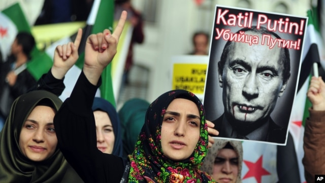 """FILE - Turkish protesters shout anti-Russia slogans as they hold a poster of Russian President Vladimir Putin that reads in Turkish and Russian """"Assassin Putin!"""" during a protest in Istanbul, Turkey, Nov. 27, 2015."""