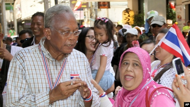 Anti-government protest leader Suthep Thaugsuban, left, poses for a photograph with a supporter during a rally, May 8, 2014 in Bangkok.