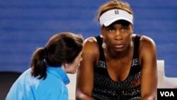 Venus Williams berkonsultasi dengan pelatih fisik sebelum mengundurkan diri dari pertandingan babak ketiga melawan petenis Jerman Andrea Petkovic akibat cedera di Kejuaraan Tenis Australia Terbuka hari Jumat (21/1).
