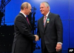 FILE - Russian President Vladimir Putin presents ExxonMobil CEO Rex Tillerson with a Russian medal, June 21, 2012.
