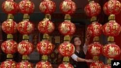 A shopkeeper arranges Chinese New Year decorations in Tainan, southern Taiwan, January 28, 2011