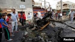 Warga bergabung di dekat serangan bom di distrik Kamaliya, Baghdad (20/5). 31 orang dilaporkan tewas dalam serangan bom di Baghdad dan Basra, Irak.