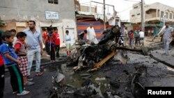 Warga berkumpul di lokasi ledakan bom bunuh diri di distrik Kamaliya, Baghdad, Senin (20/5). Serangan di Baghdad menewaskan sedikitnya 48 orang.
