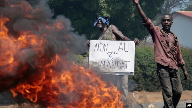 "FILE - An opposition demonstrator holds a sign in French reading ""No to a third term"" next to a barricade fire set by protesters in the Ngagara neighborhood of Bujumbura, Burundi, June 3, 2015."