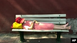An unidentified girl takes a nap on a bench along the red walls next to Tiananmen Gate in Beijing Sunday, July 15, 2001. (AP Photo/Vincent Yu)