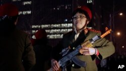 In this Tuesday, March 24, 2015 photo, Chinese women wearing military costume march with toy guns during their daily exercises at a square outside a shopping mall in Beijing.
