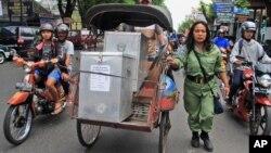 Seorang petugas mengawal becak yang membawa kotak-kotak suara untuk didistribusikan ke TPS-TPS di Yogyakarta (8/7).