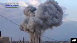 FILE - An image by Syrian activists purports to show smoke rising after a Russian airstrike hit buildings in the town of Latamna, near Hama in eastern Syria, Oct. 7, 2015.