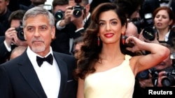 George Clooney and his wife, Amal .