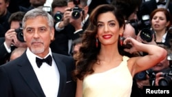FILE - George Clooney and his wife, Amal, pose on the red carpet during the 69th Cannes Film Festival in Cannes, France, May 12, 2016.