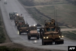 FILE - A convoy of U.S. military vehicles is seen in Syria's northern city of Manbij, Dec. 30, 2018.