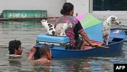 Cư dân địa phương đưa chó mèo và đồ tùy thân lên thuyền đi tìm nơi tránh lụt ở Ayutthaya, Thái Lan, 9/10/2011