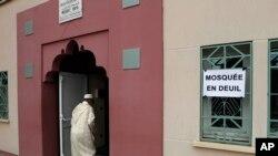 """Seorang jamaah masjid berjalan melewati sebuah poster bertuliskan """"Masjid Berduka"""" untuk melaksanakan sholat Jumat di Masjid Yahya, di Saint-Etienne-du-Rouvray. Normandy, Perancis (Foto: AP Photo/Francois Mori)"""