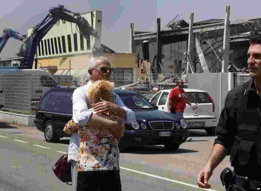 Un poblador de Mirandola de apellido Borghi, quien perdió a un hijo en el terremoto, trata de consolar a su esposa frente a la fábrica de molduras BBG que resultó destruida por el temblor en el norte de Italia este martes 29 de mayo d