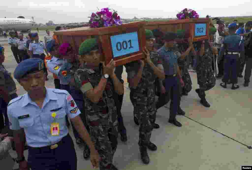 Militares indonésios carregam caixões contendo corpos de dois passageiros, que iam a bordo do AirAsia 8501, recuperados na costa de Bornéu, na base militar de Surabaya. O avião da Air Asia caiu a 28 de Dezembro. Indonésia Dez. 31, 2014.
