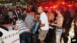 Одного из пострадавших вынесли из ночного клуба «Кисс» для оказания ему медицинской помощи. Санта-Мария. Бразилия. 27 января 2013 г.