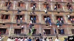 FILE - Indians climb the wall of a building to help students appearing in an examination in Hajipur, in the eastern Indian state of Bihar, March 18, 2014.