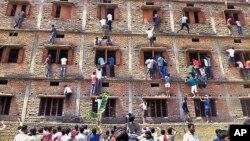 Sejumlah warga memanjat dinding bangunan untuk membantu para siswa menempuh ujian di Hajipur, negara bagian Bihar, India, 18 Maret 2015 (AP Photo/Press Trust of India, File).