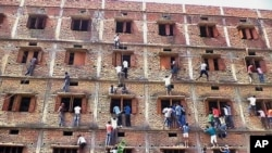 Indians climb the wall of a building to help students taking an examination in Hajipur, in India's Bihar state, March 18, 2015