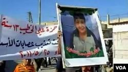 Demonstran anti-pemerintah Suriah membawa poster Hamza al-Khatib, anak laki-laki yang menjadi korban tewas kekerasan di Daraa.