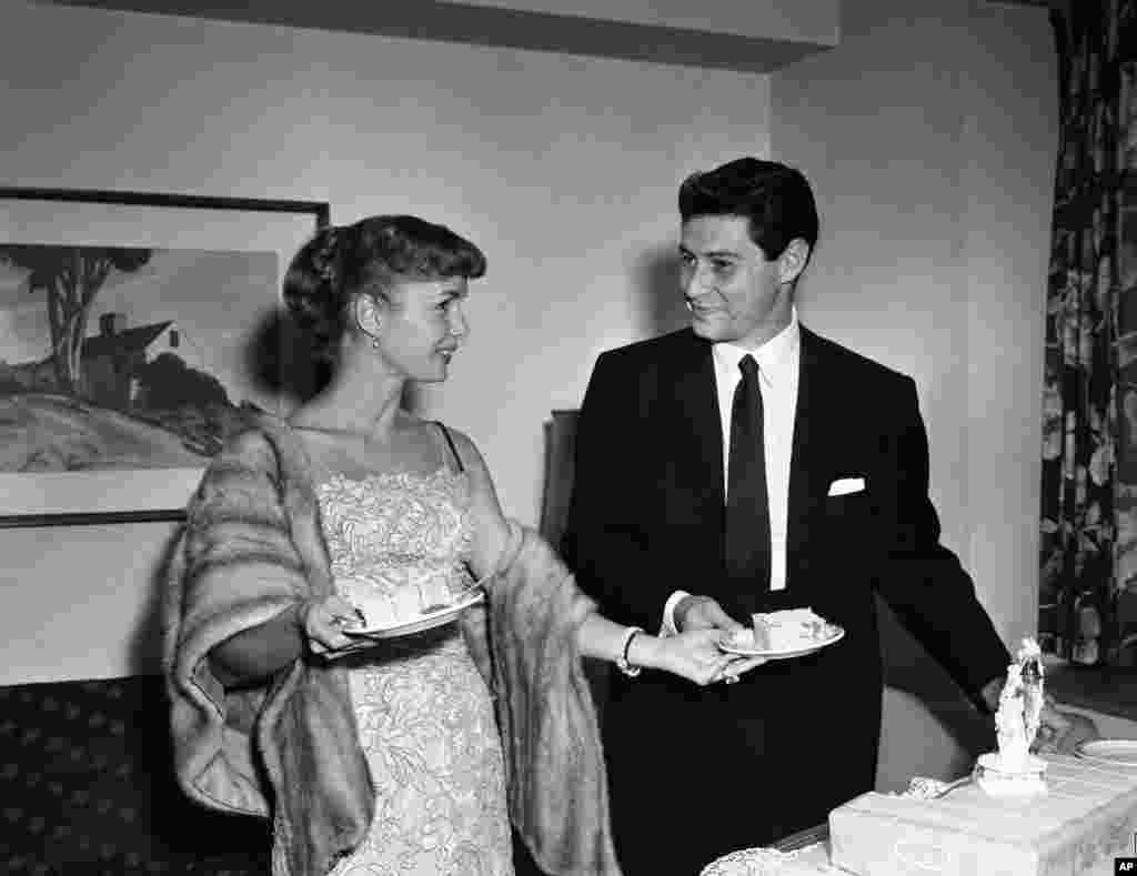 Actress Debbie Reynolds hands her singing husband Eddie Fisher a piece of cake as they pose at a press conference in Washington, D.C., about 24 hours after their marriage at a Catskill mountain resort, Sept. 27, 1955.