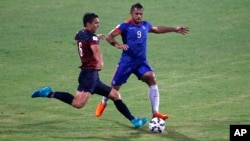 FILE - India's Robin Singh, right, and Guam's Mason Douglas in action as it rains during their 2018 FIFA World Cup qualifying soccer match in Bangalore, India, Nov. 12, 2015.