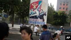 FILE - A man sits under a propaganda banner in Pyongyang, North Korea, Aug. 23, 2015.
