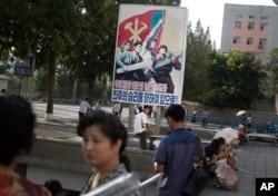 A man sits under a propaganda banner in Pyongyang, North Korea, Aug. 23, 2015.