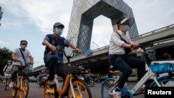 人们骑车路过位于北京中央商业区的中国官媒央视大楼。