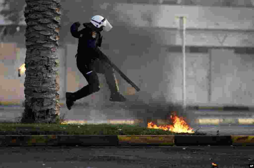 Một cảnh sát chống bạo loạn nhảy tránh một bom xăng do các người biểu tình chống chính phủ Bahrain ném trong cuộc đụng độ tại Diaz, Bahrain. Xung đột bùng phát sau đám tang của Abdul Ghani al-Rayes, mà theo lời thân nhân và các nhà hoạt động ông bị xỉu và chết bên ngoài một trạm cảnh sát.