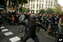 A Spanish riot policeman swings a club against would-be voters near a school assigned to be a polling station by the Catalan government in Barcelona, Oct. 1, 2017.