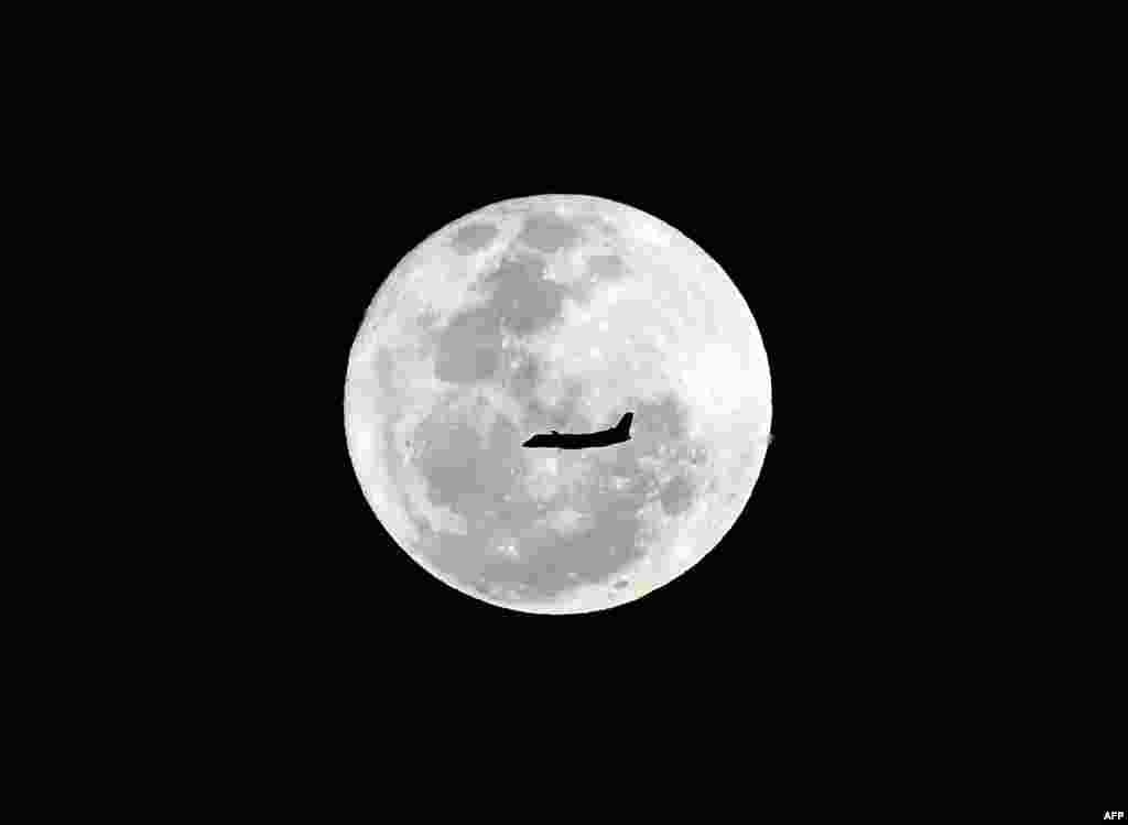 A plane flies in front of a full moon in Sydney, Australia.