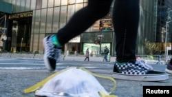 2020年3月14日,一名女子从特朗普大厦附近街面上一个用过的防护口罩旁走过。