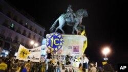 Para pengunjuk rasa menempatkan spanduk di patung Raja Carlos III sebagai bagian dari protes anti langkah penghematan di Puerta del Sol Plaza, Madrid, Sabtu (12/5).